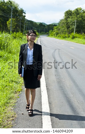 Beautiful Asian business woman walking lonely on business way.