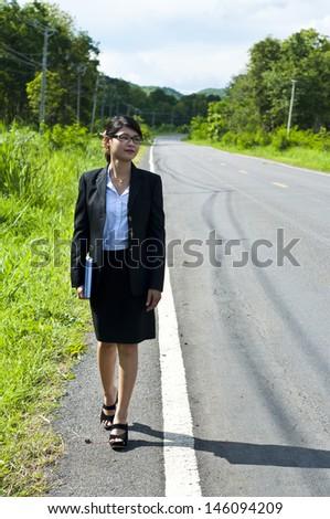 Beautiful Asian business woman walking lonely on business way. - stock photo