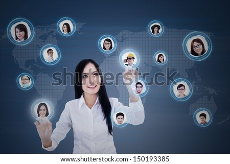 Beautiful Asian businesswoman clicking on digital social network on blue background   - stock photo