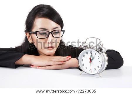 Beautiful asian businesswoman looking at alarm clock - stock photo