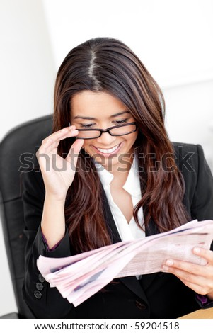 beautiful asian businesswoman reading the news in her office - stock photo
