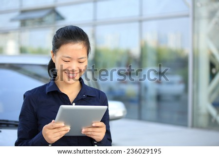 beautiful asian businesswoman use digital tablet leaning on car outside of office building