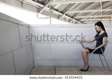 beautiful asian businesswoman working on her laptop outdoor