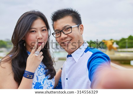 Beautiful Asian couple of tourists spending their vacation in Paris and taking selfie with a mobile phone, girl is showing a V sign, a popular gesture in photographs in Asian countries - stock photo