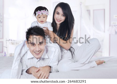 Beautiful asian family playing together in the bedroom, looking at camera - stock photo