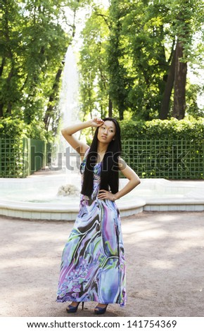 Beautiful Asian fashion model posing in blue dress. Outdors. Summer park. - stock photo