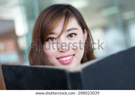beautiful asian female student reading book in library - stock photo