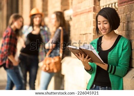 Beautiful asian female student with tablet at the college, outdoors. Her classmates in the background. - stock photo