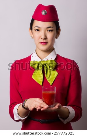 Beautiful Asian flight attendant holds a glass of tomato juice in hand - stock photo