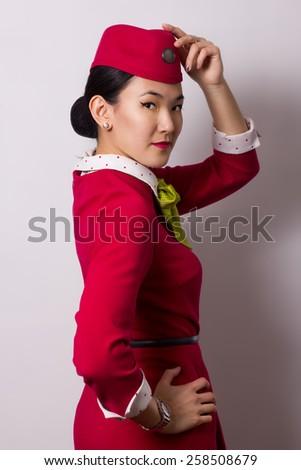 Beautiful Asian flight attendant on grey background - stock photo