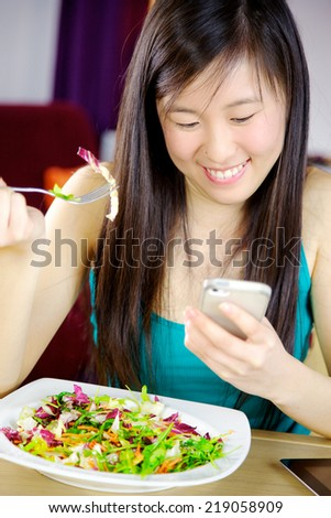 beautiful asian girl having fun texting on a cellphone while having lunch