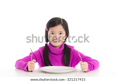 Beautiful asian girl holding a spoon and fork with empty white plate on white background isolated - stock photo