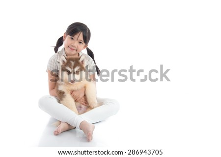 Beautiful asian girl hugging siberian husky puppy on white background isolated with copy space on right - stock photo
