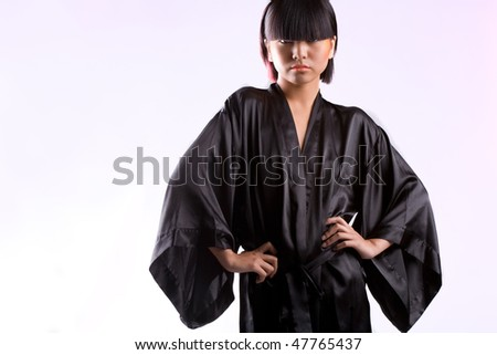 Beautiful Asian girl in black robe on white studio background