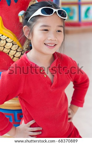 Beautiful asian girl in red suit at Chinese temple, Thailand.