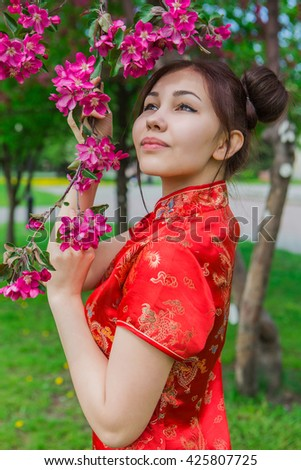 Beautiful asian girl in traditional chinese red dress near pink apple tree in the park.