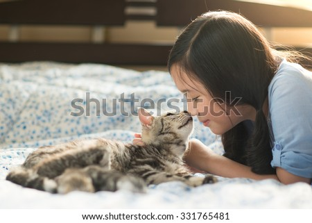 Beautiful asian girl kissing american shorthair cat on the bed - stock photo