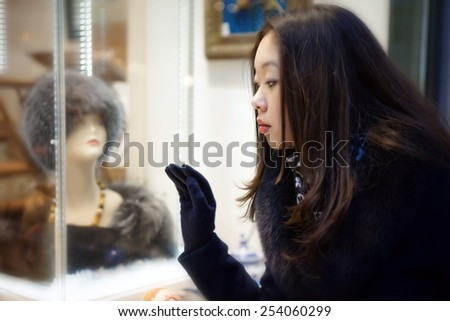 Beautiful Asian girl looking at shop window - stock photo