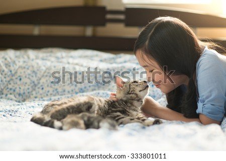 Beautiful asian girl lying with american shorthair cat on the bed - stock photo