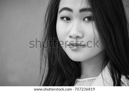 Beautiful Asian girl on the background of the business center wall. Black and white photography