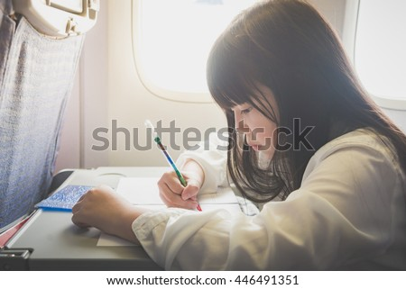 Beautiful Asian girl painting with color pencil on airplane - stock photo