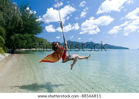 Beautiful asian girl play swing at the sea - stock photo