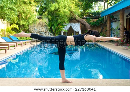 Beautiful Asian Girl practicing virabhadrasana III (warrior III) yoga pose by the pool  - stock photo