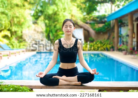 Beautiful Asian Girl practicing yoga by the pool, lotus pose on a bench (padmasana) - stock photo