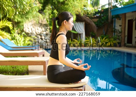 Beautiful Asian Girl practicing yoga by the pool, lotus pose (padmasana) - stock photo