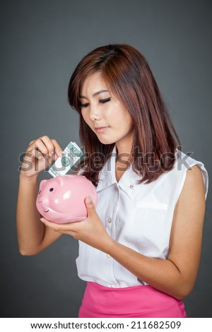 Beautiful Asian girl put a bill to pink pig money box on gray background