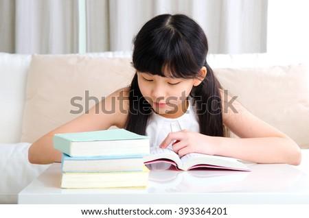 Beautiful asian girl reading book at home - stock photo