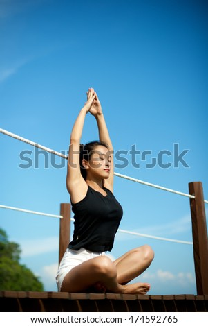Beautiful Asian girl relax and doing yoga at the pier