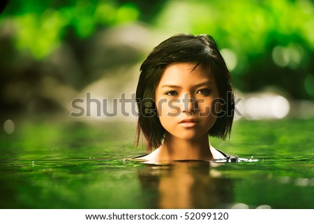 Beautiful Asian girl rises up out of stream - stock photo
