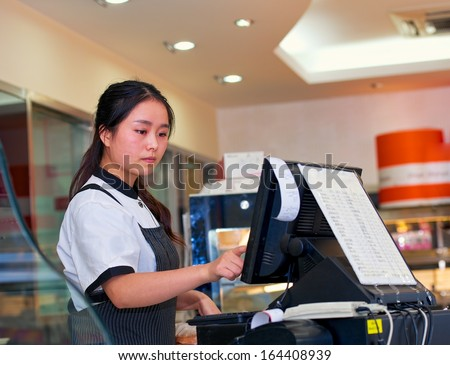 beautiful asian girl seller in the coffee shop - stock photo