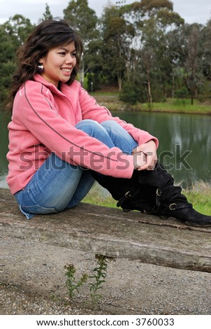 Beautiful asian girl sitting on a bench