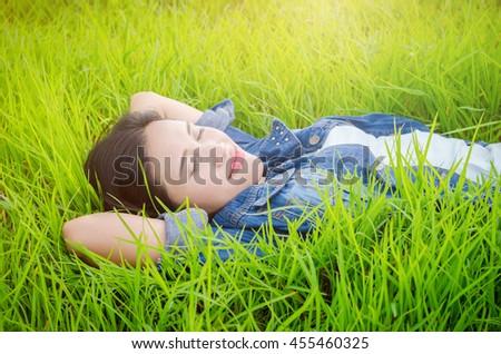 Beautiful asian girl sleeping on grass field