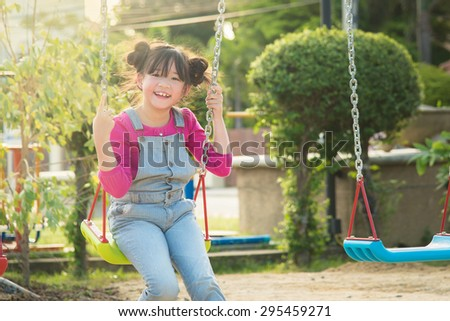 Beautiful asian girl swinging on the playground with big nice toothy smile on sunny day