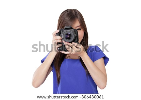 Beautiful Asian girl taking a picture using her digital camera, aiming focus at you, isolated on white background - stock photo