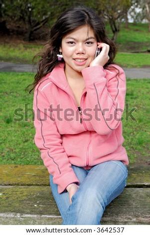 Beautiful asian girl talking on a phone - stock photo