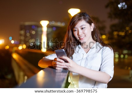 beautiful asian girl using mobilephone leaning against railing on square at night - stock photo