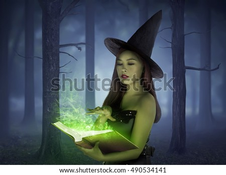 Beautiful asian girl wearing witch cloth reading spell in the book on the forest at night