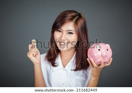 Beautiful Asian girl with a coin and  pink pig money box on gray background - stock photo