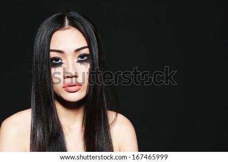 Beautiful Asian girl with black mascara running under eyes