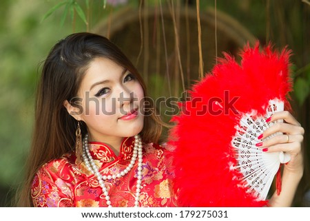 Beautiful Asian girl with Chinese traditional dress Cheongsam holding a Chinese Fan - stock photo