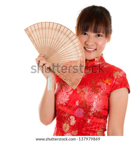 Beautiful Asian girl with Chinese traditional dress Cheongsam holding a Chinese Fan isolated on white background - stock photo