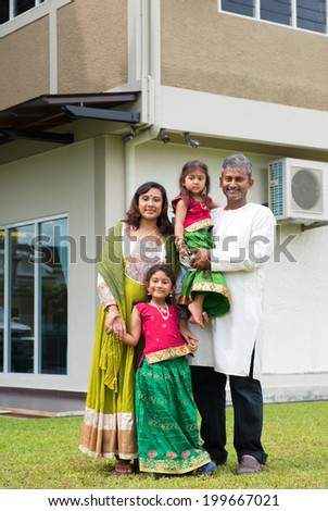 Beautiful Asian Indian family portrait smiling outside their new house.
