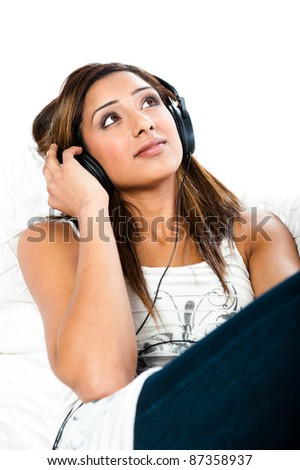 Beautiful asian indian teenage girl, listening to music with her eyes open sitting - stock photo