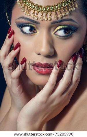 Beautiful asian/indian woman with bridal makeup and jewelry, closeup shot - stock photo