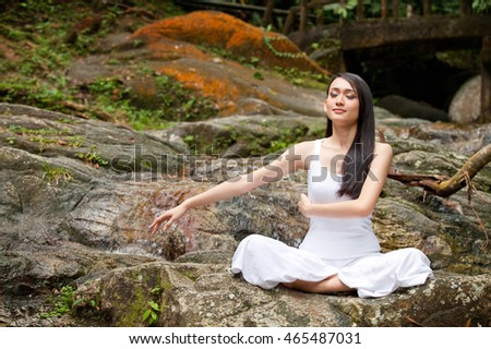 Beautiful asian lady practising yoga outdoor