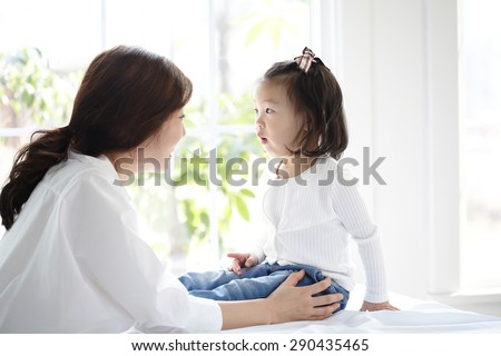 beautiful Asian mom and her cute daughter kissing with love while looking at each other - stock photo